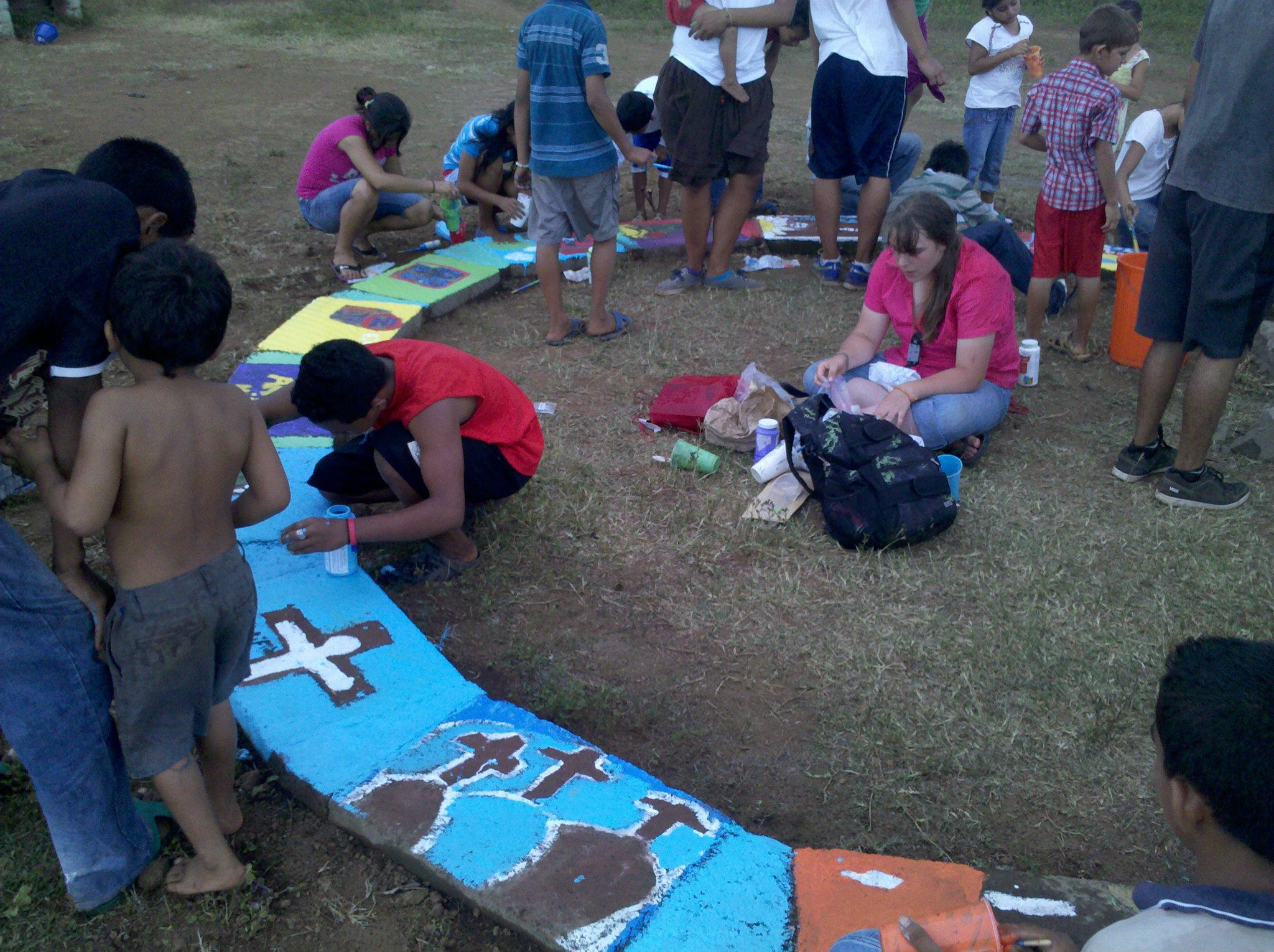 Children painting the finished construction project at the center of Barrio Nuevo.